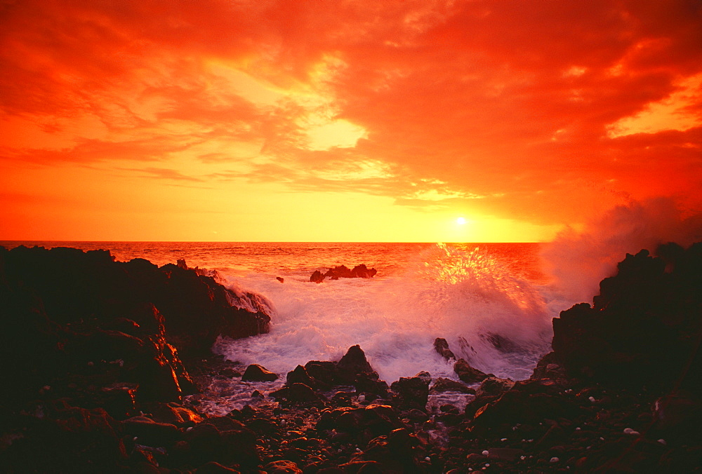 Hawaii, Big Island, Kona, Keahou, Sunset and surf on rocks.