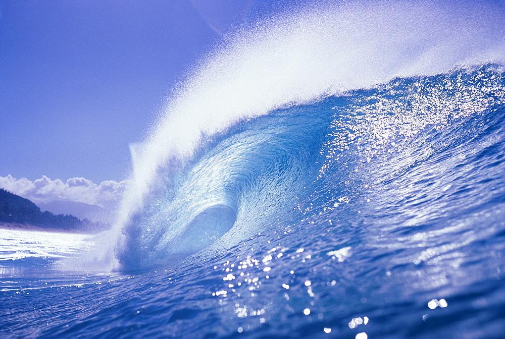 Large curling glassy wave, slight glimpse of land.