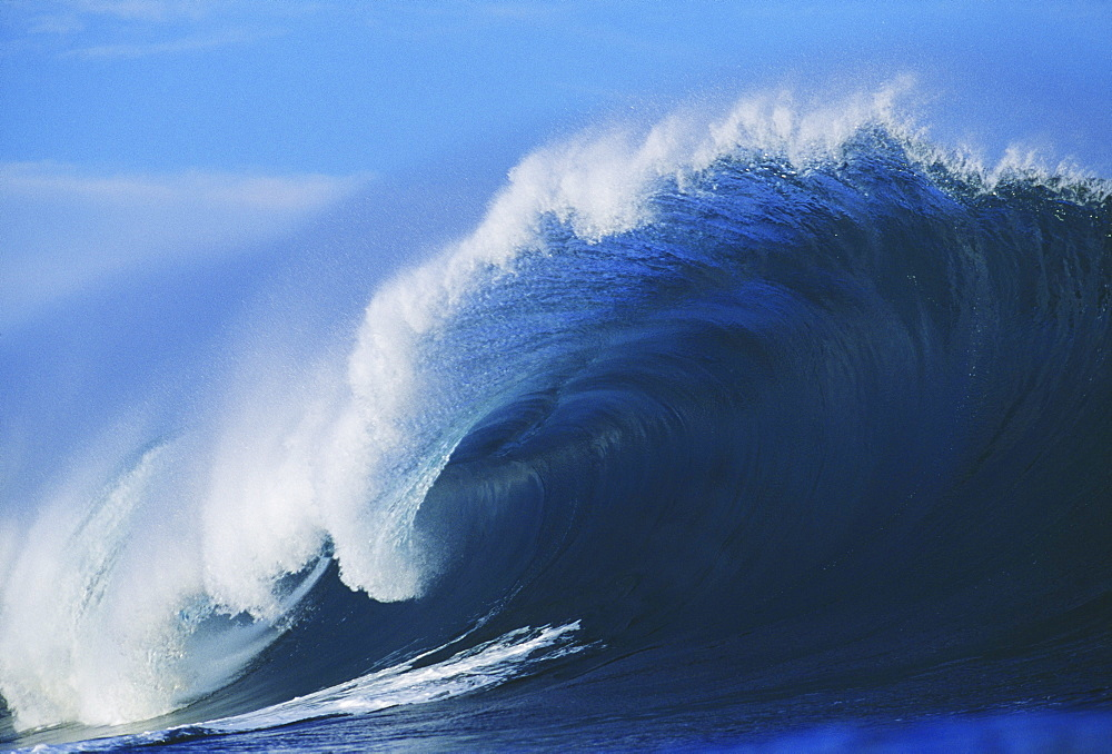 Hawaii, Oahu, North Shore, Pipeline, big blue wave curling with mist blowing off tip