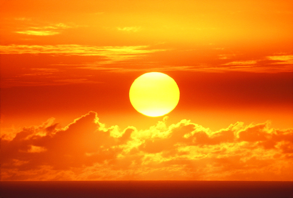 Hawaii, Oahu, Waikiki, View of huge orange sun sinking towards the horizon.