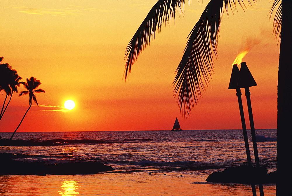 Hawaii, Big Island, Kohala, Waiulua Bay, Orange sunset with palm trees, sailboat and tiki torches.