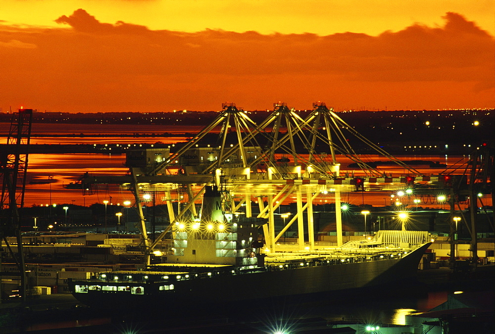 Hawaii, Oahu, Bright lights of a container ship at dusk in Honolulu Harbor.