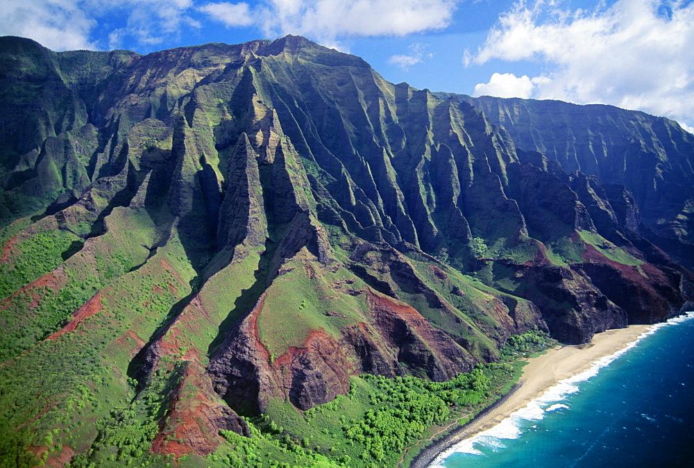Hawaii, Kauai, NaPali Coast aerial along cliff, mountains with jagged cliffs, secluded beach