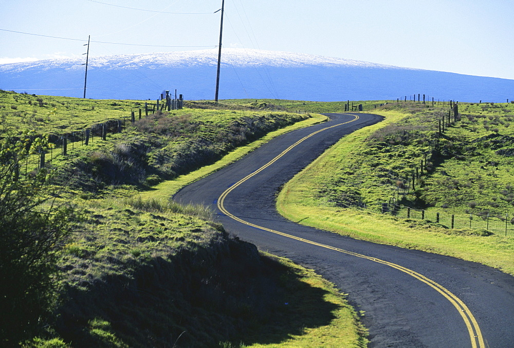Hawaii, Big Island, Saddle Road curves it's way towards snowcapped Mauna Loa.