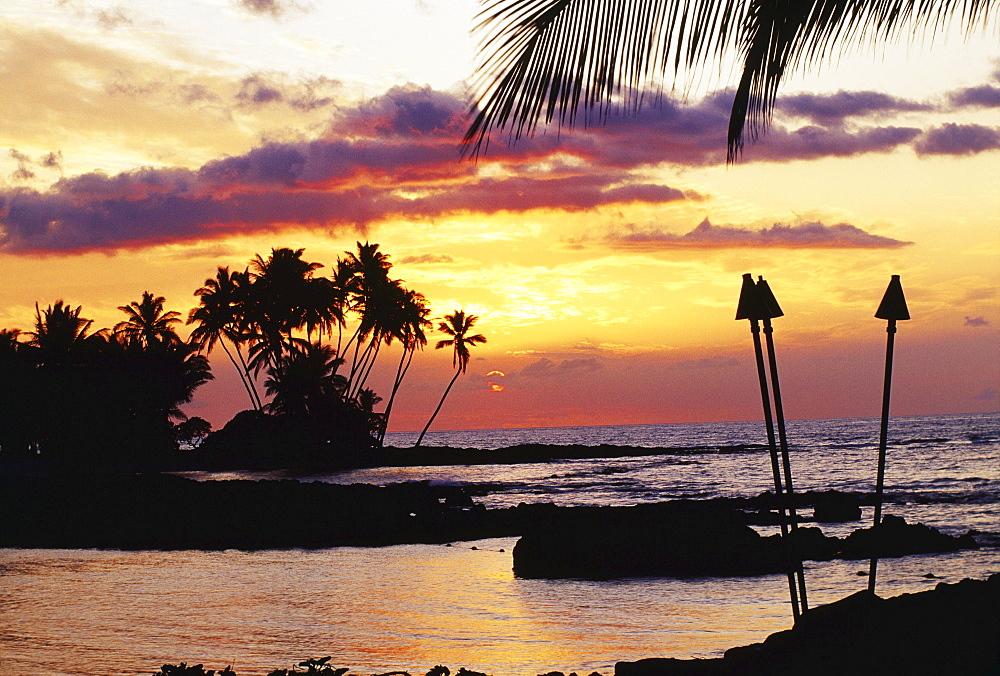 Hawaii, Big Island, Kohala, Waiulua Bay, Orange sunset with palm trees and tiki torches.