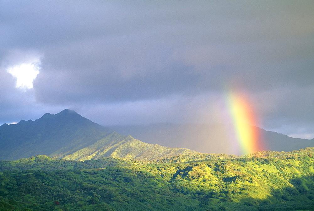 Hawaii, Kauai, end of rainbow lands in Hanalei Valley, large gray clouds