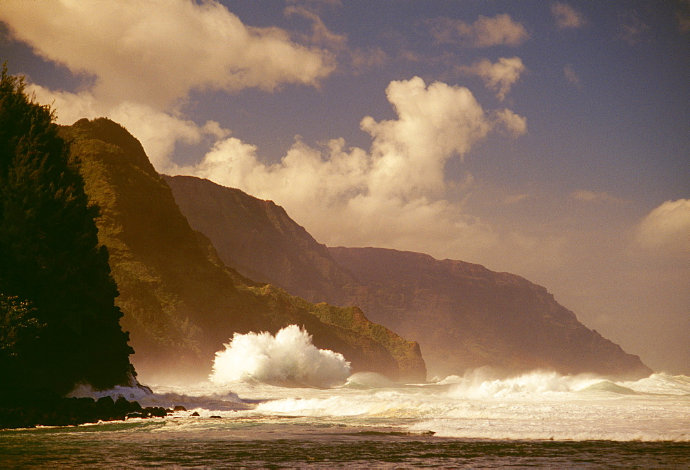 Hawaii, Kauai, NaPali Coast Storm surf pounding along shoreline, moody skies