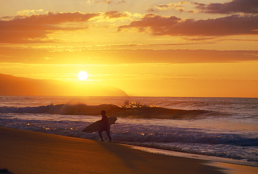 Hawaii, Oahu, North Shore, Silhouette of surfer walking out of ocean at golden sunset