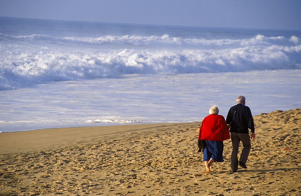 View from behind senior couple walking on beach, arm in arm white shorebreak ocean water