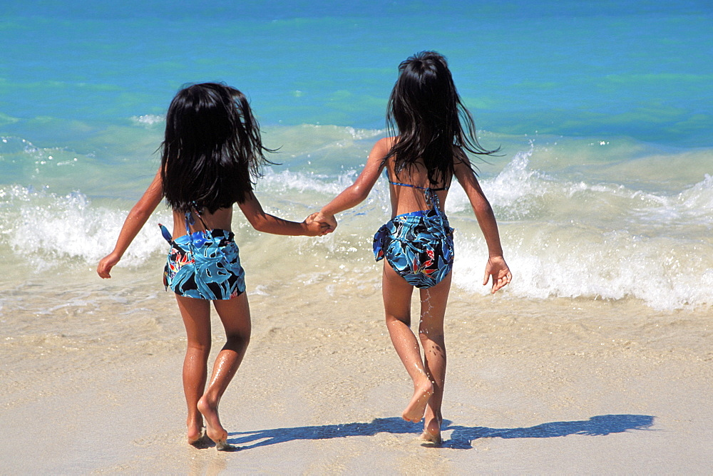 Hawaiian girls running into shoreline, view from behind, matching outfits