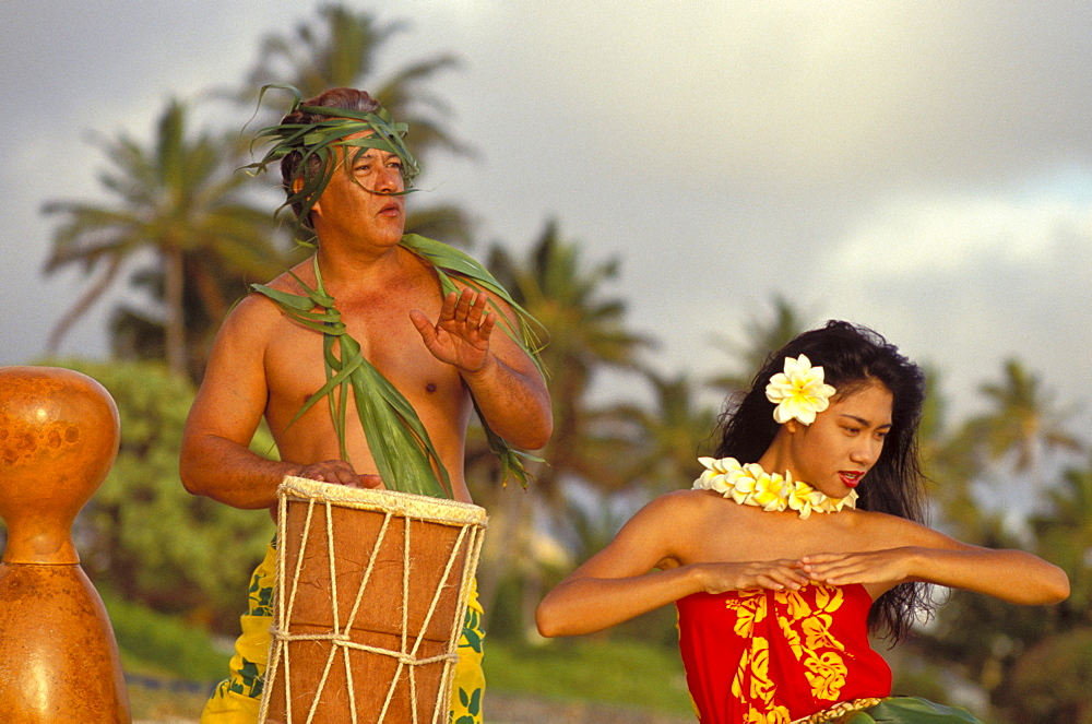 Hula at sunrise on beach with Tahitian Drummer dancing and playing with pride