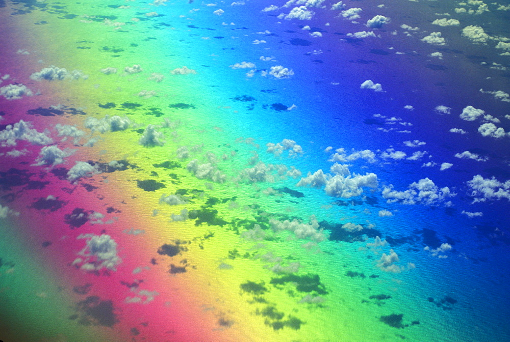 Polarized rainbow and aerial of clouds over the ocean