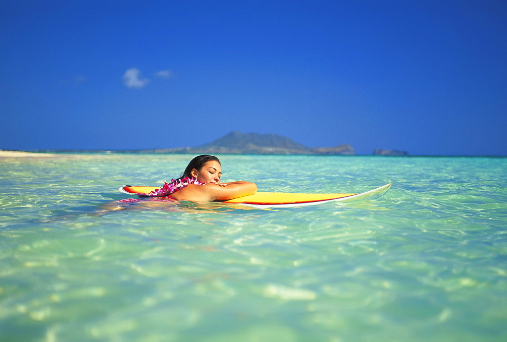 Hawaii, Oahu, Lanikai, Woman eyes closed resting head/arms on surfboard on clear water.