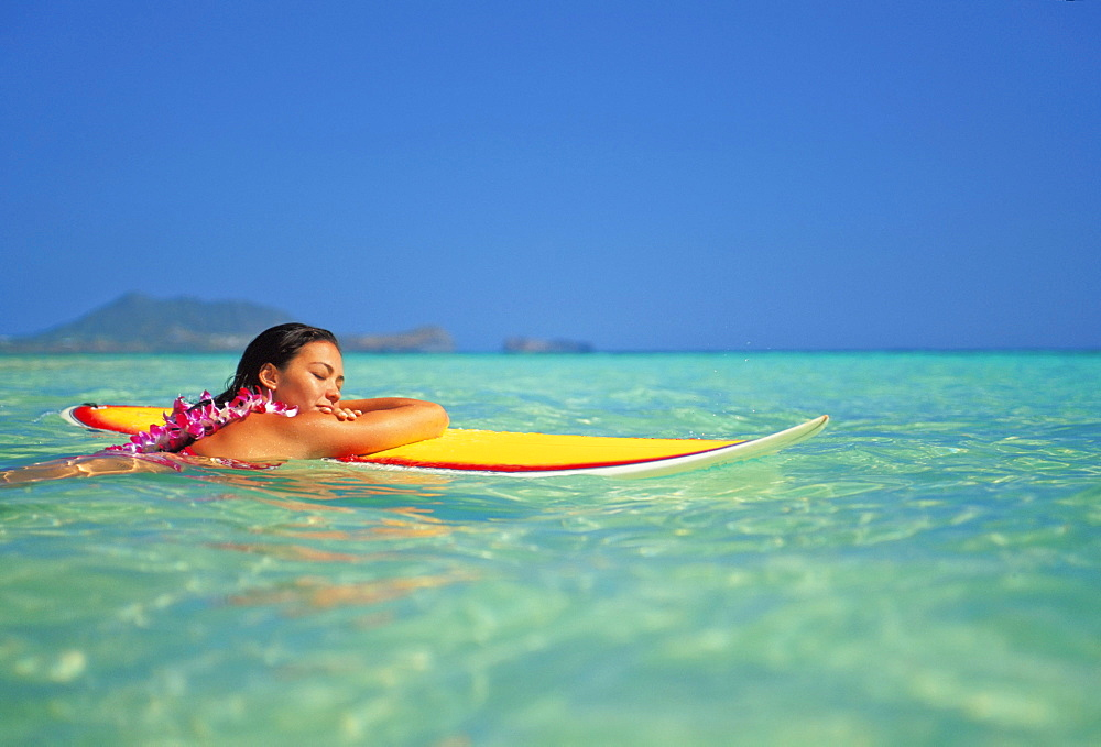 Hawaii, Oahu, Lanikai, Woman resting face of surfboard while in ocean with eyes closed