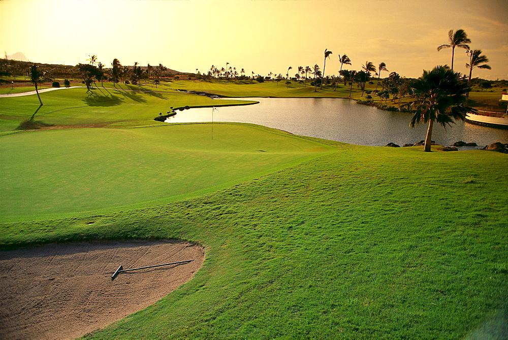 Hawaii, Oahu, Kapolei, Ko'Olina Golf Club, 18th hole at twilight, water hazard, sand trap