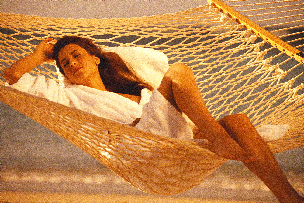 Woman in white terry robe relaxes in rope hammock, golden light  - 1116-38401