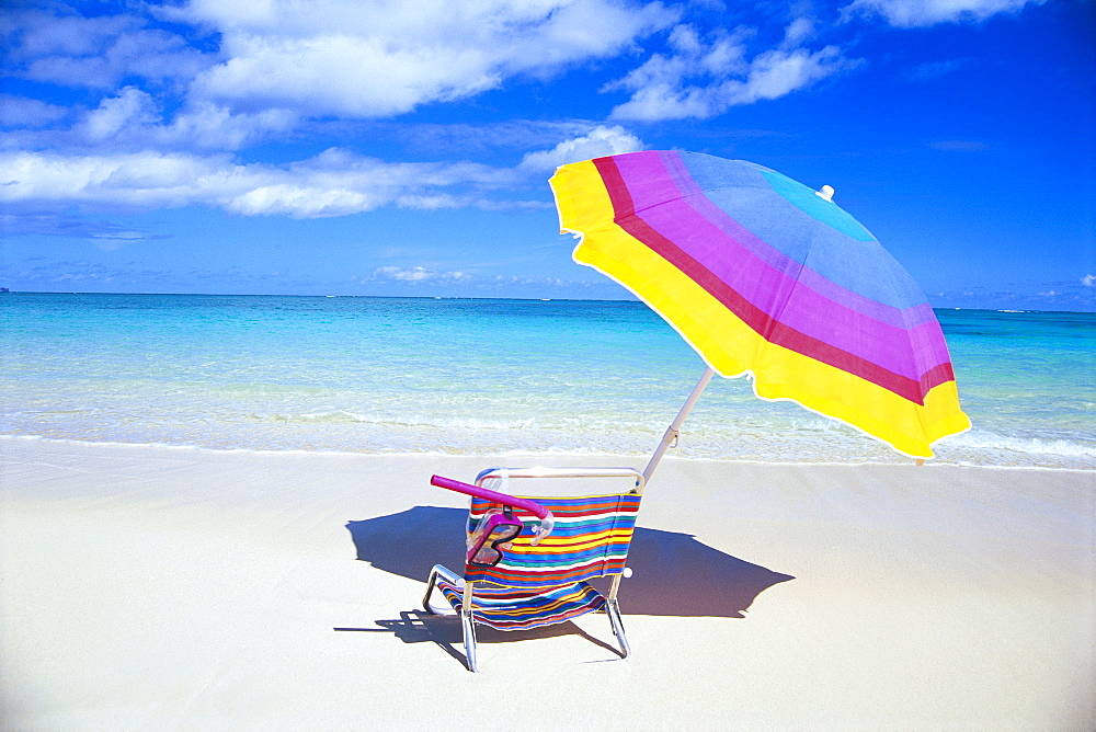 Beach chair and umbrella with snorkel gear, turquoise ocean and blue skies