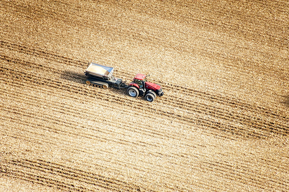 Aerial view of a tractor in a field pulling a grain wagon loaded with freshly harvested soybeans in Kent County; Rock Hall, Maryland, United States of America