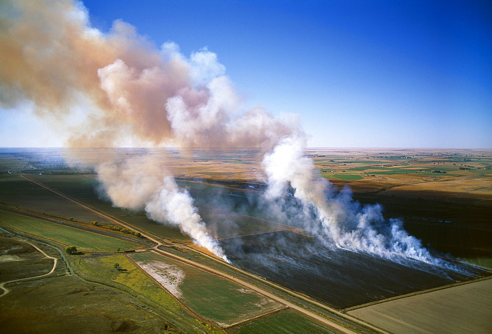 Agriculture - Aerial view of a field of grain stubble being burned / near Lamar, Colorado, USA.