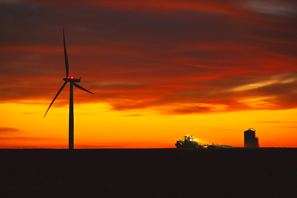 Agriculture - A farmer tills his field at dusk after corn harvest in late Autumn, below an electric wind turbine, illustrating the coexistence of traditional and modern or
