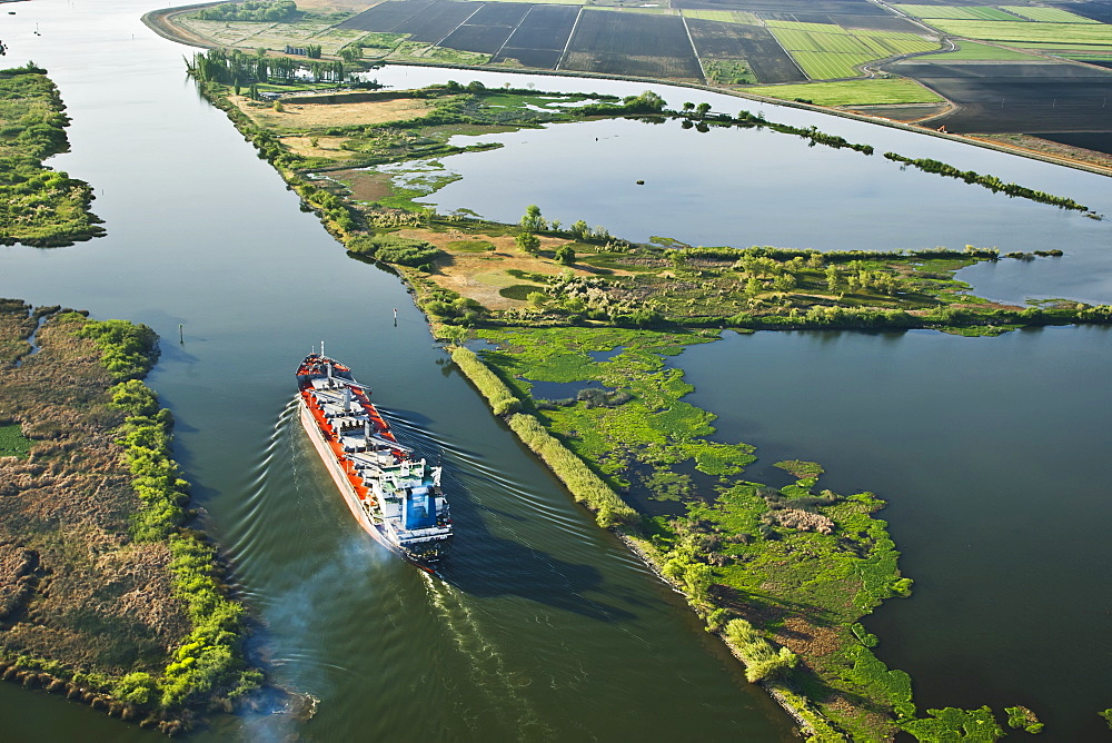 Agriculture - Aerial view of an ocean going grain ship transiting the deep water channel in the Sacramento-San Joaquin River Delta between the Port of Sacramento and the San Francisco Bay and Pacific Ocean / California, USA. - 1116-39052