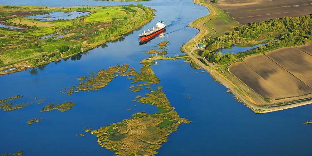 Agriculture - Aerial view of an ocean going grain ship transiting the deep water channel in the Sacramento-San Joaquin River Delta between the Port of Sacramento and the San Francisco Bay and Pacific Ocean / California, USA.