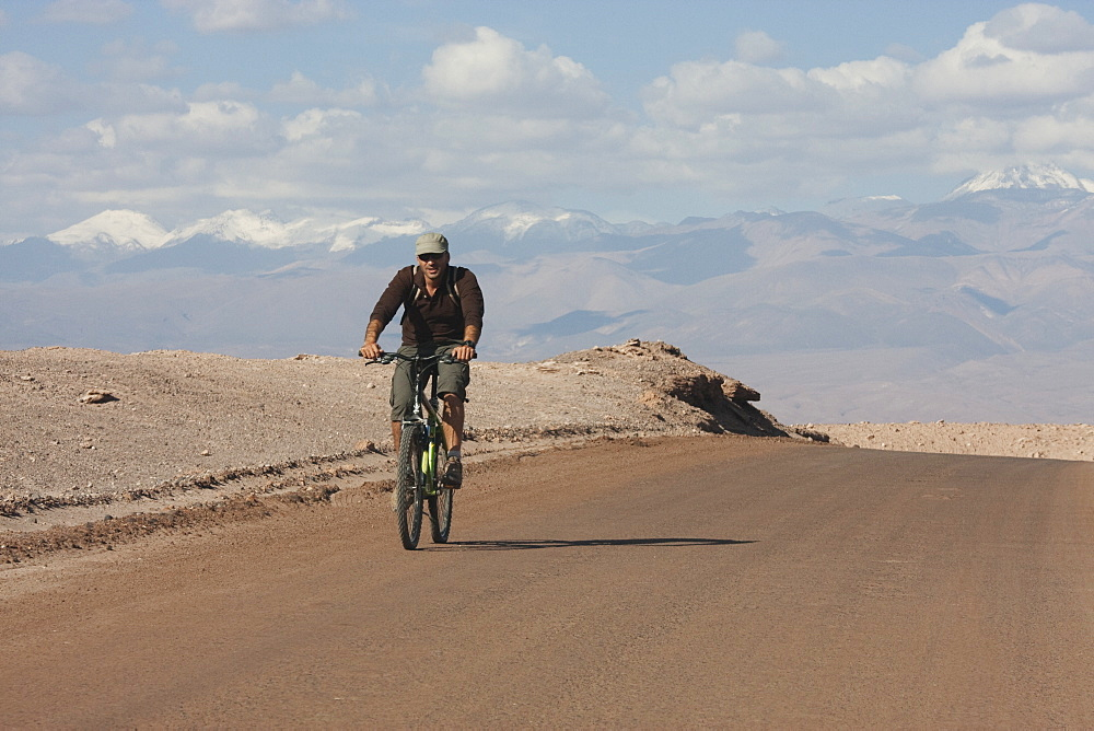 Man On A Mountain Bike Travelling Through The Valle De La Luna (Moon Valley), San Pedro De Atacama, Antofagasta Region, Chile
