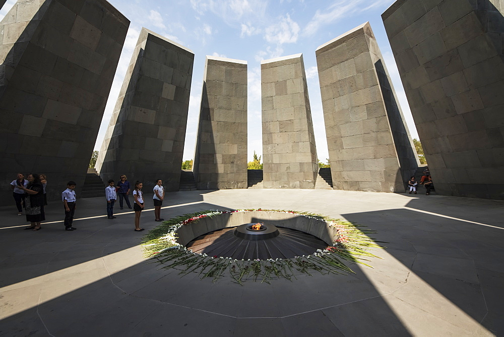 School children standing by the eternal flame dedicated to the 1.5 million people killed during the Armenian Genocide in the Armenian Genocide memorial complex on Tsitsernakaberd hill, Yerevan, Armenia