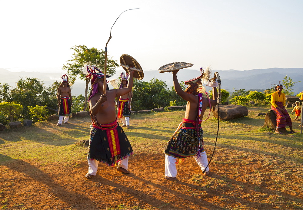 Manggarai men wearing traditional headdress wrapped with cloth using shields and bamboo whips in a caci, a ritual whip fight, Melo village, Flores, East Nusa Tenggara, Indonesia