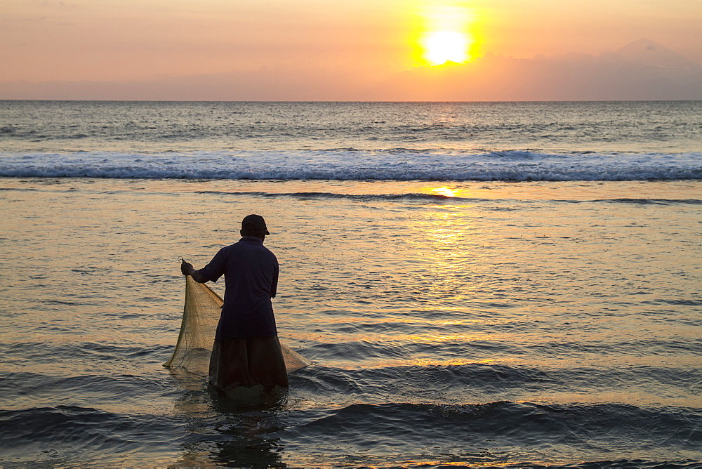 Fisherman casting his net in the ocean at sunset, Mangsit, Lombok, West Nusa Tenggara, Indonesia