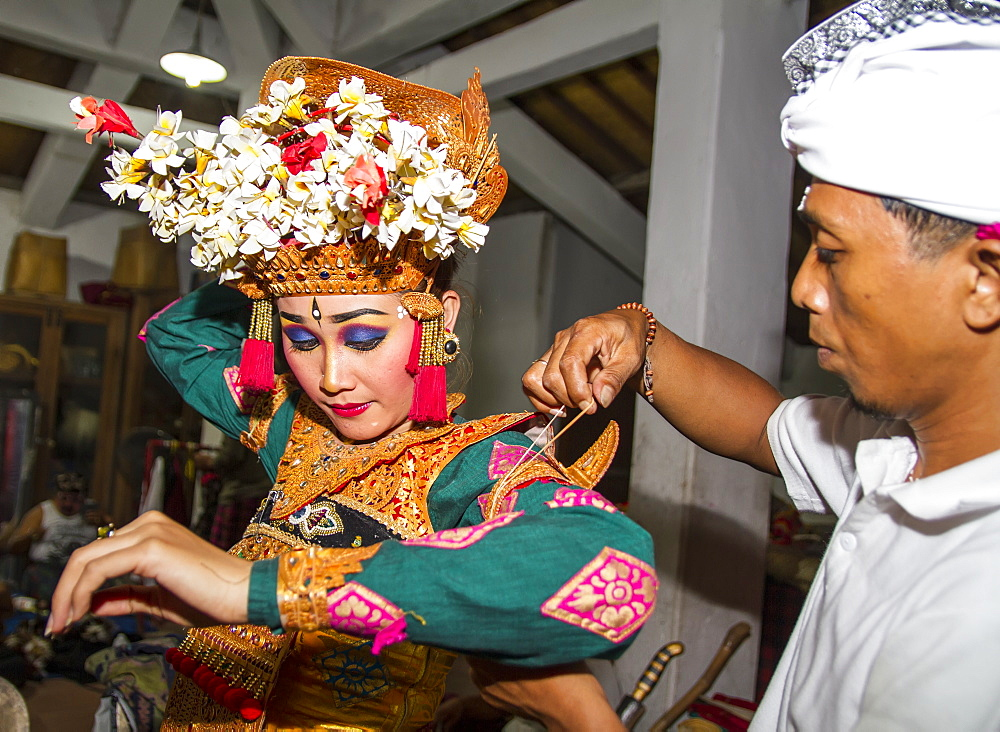 Balinese man assisting a dancer of the Raja Peni troupe with her costume before a dance performance, Ubud, Bali, Indonesia