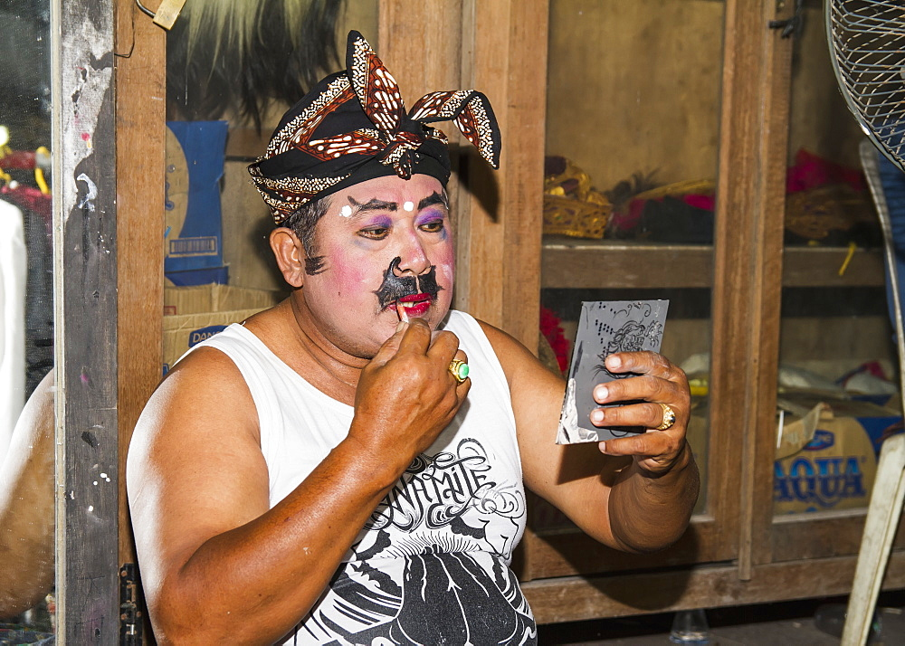 Balinese performer of the Raja Peni troupe applying make-up before a dance performance in front of a mirror, Ubud, Bali, Indonesia