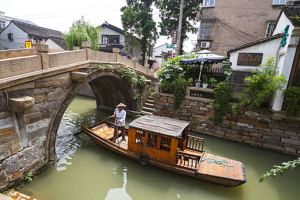 Man punting a boat by a bridge over the North-South canal by Pingjiang Road, Suzhou, Jiangsu, China