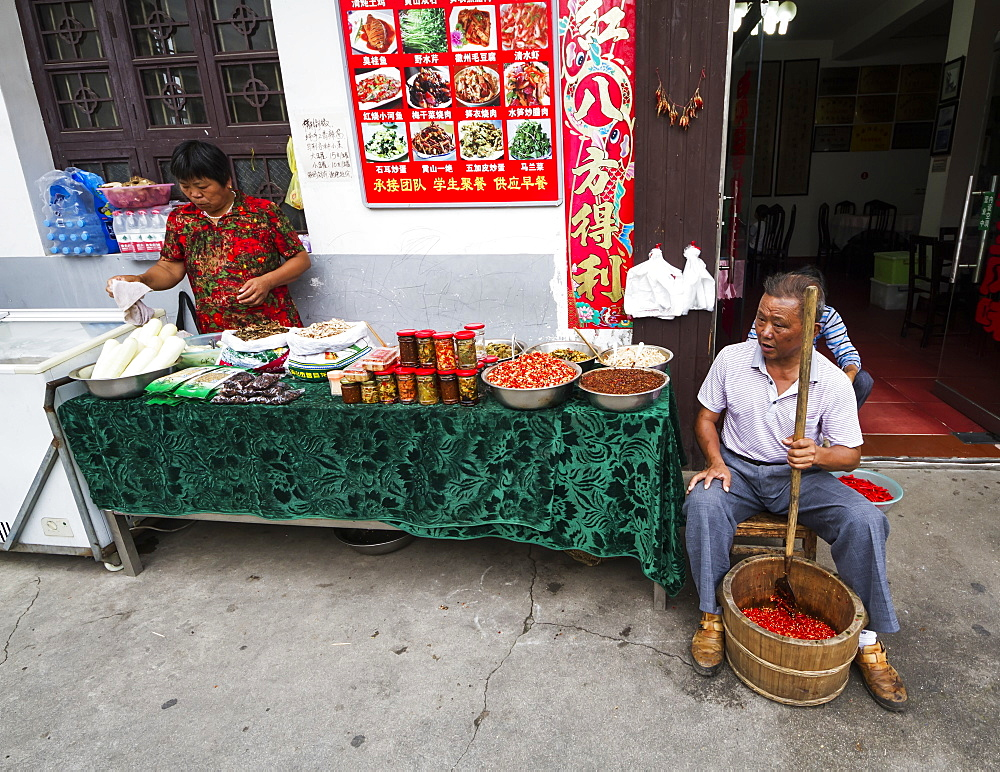 Man crushing hot peppers, Hongcun, Anhui, China - 1116-39381