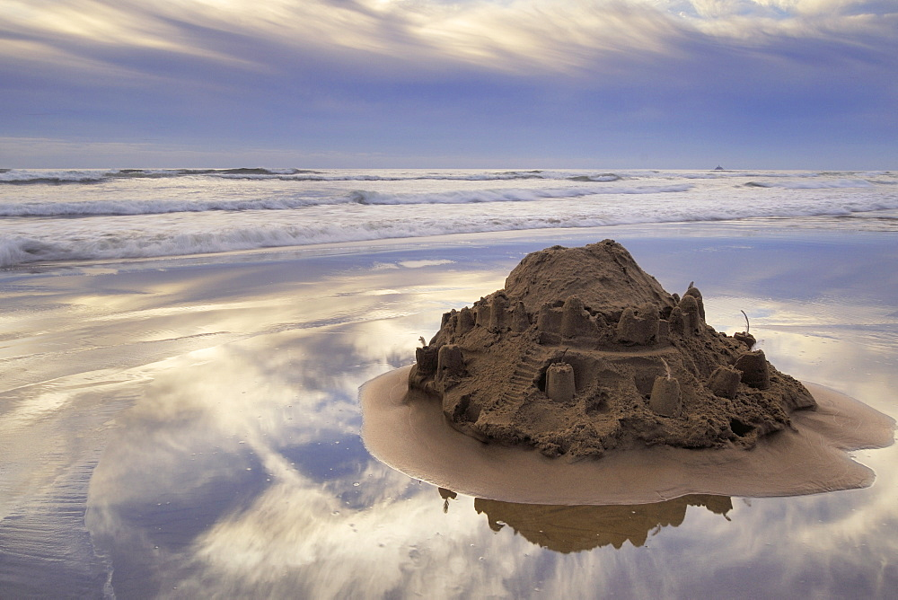 A Sandcastle Being Slowly Washed Away By The Incoming Tide, Cannon Beach, Oregon