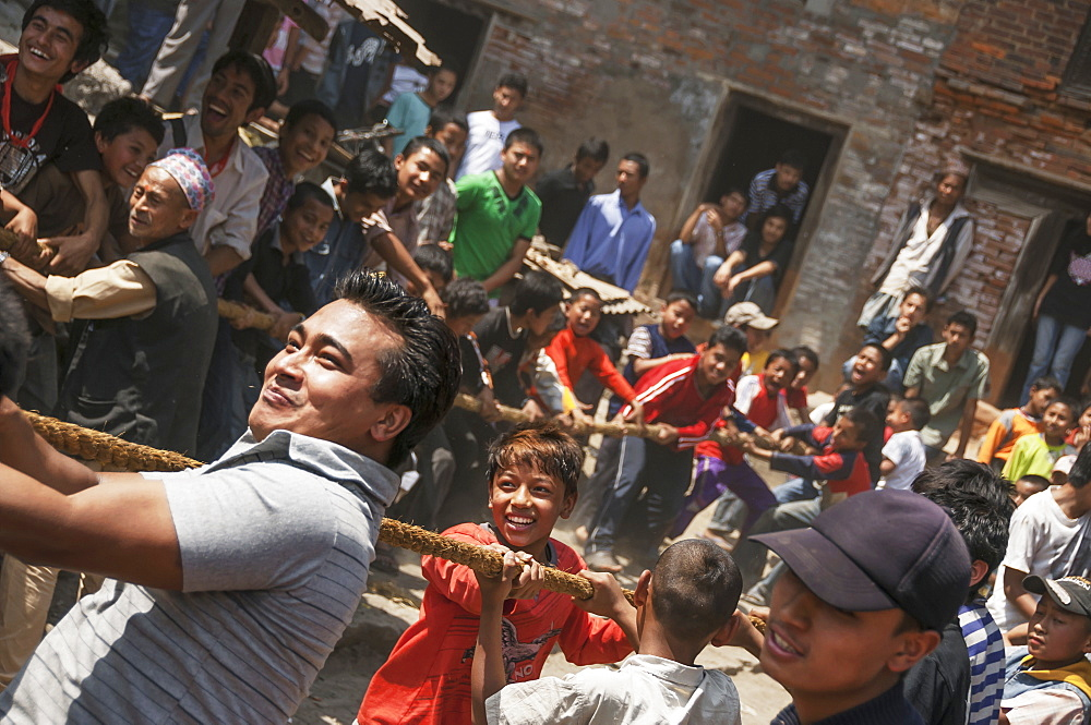 Young people pulling the strings to hoist the mast at the traditional Bisket Jatra Festival in Napalese New Year, Bhaktapur, Nepal - 1116-39410