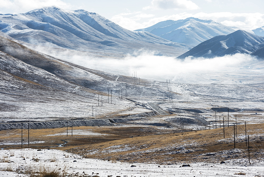 Electrical lines and poles stretch out across Tibetan mountains, Tibet
