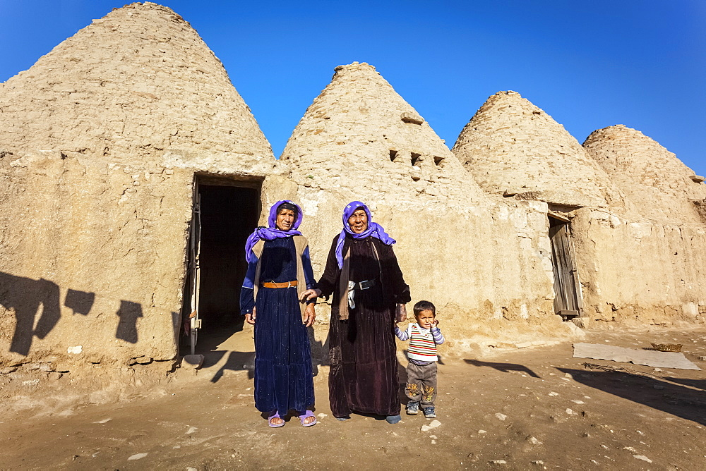 Two women and a child standing outside the doorway of a primitive dwelling, Harran, Turkey