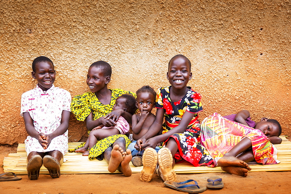 Young girls and small children sitting together on a mat against a wall, Gulu, Uganda