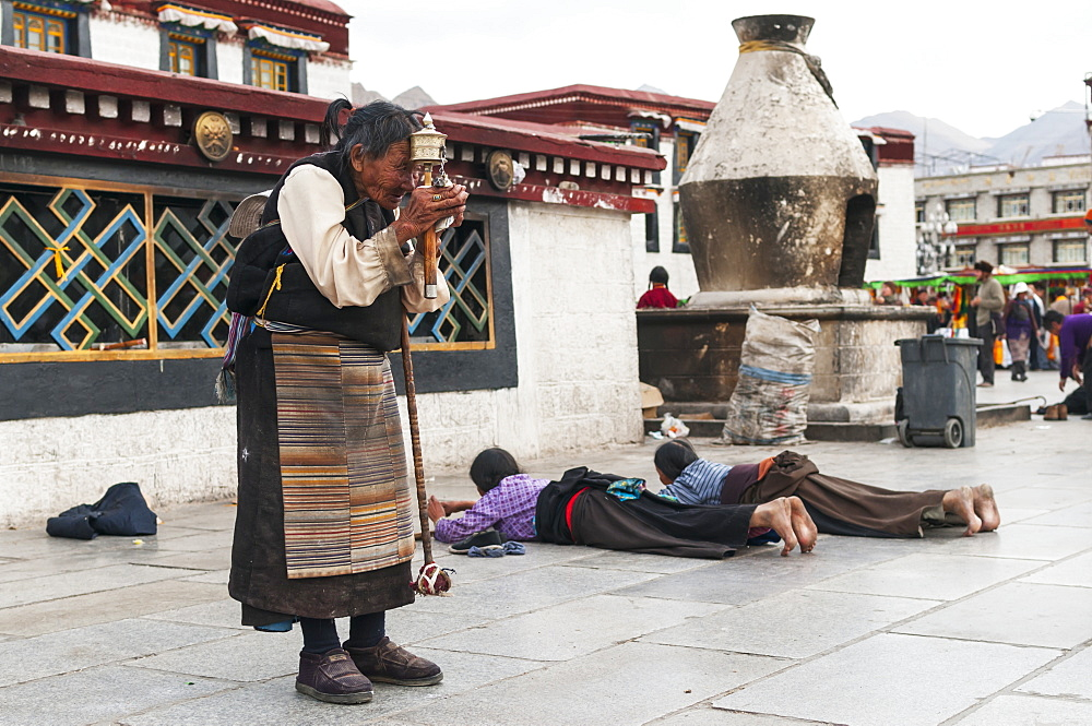 A old woman prays in front of Jokhang Temple, Lhasa, Tibet, China