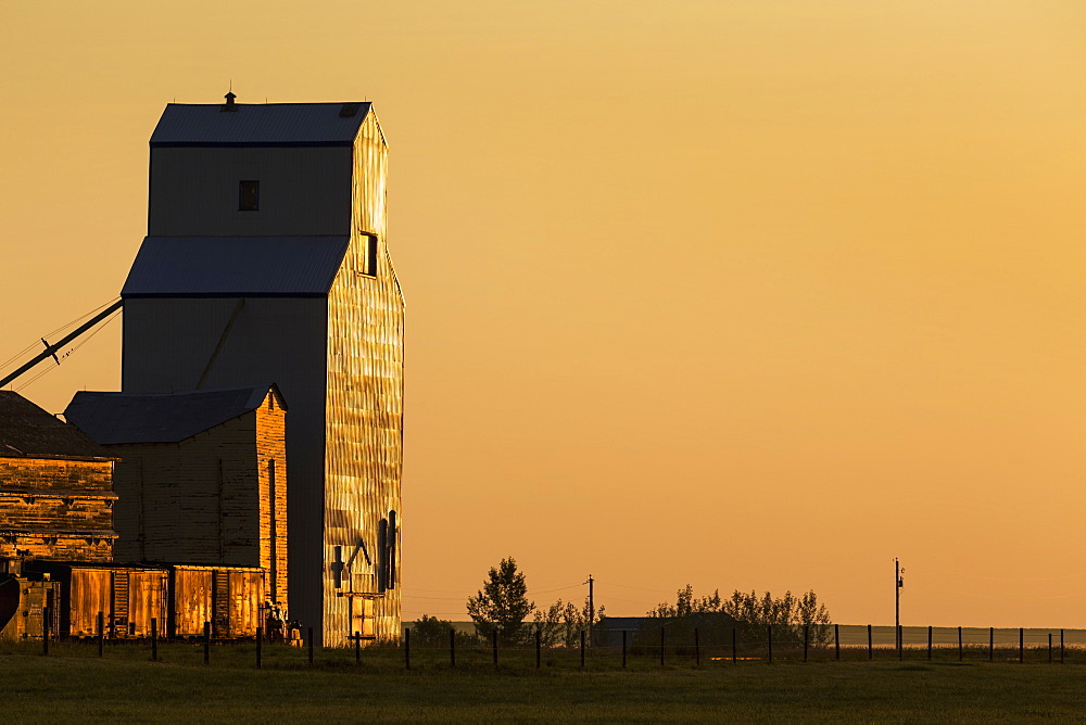 Wooden grain elevator refecting the orange glow of sunrise, Mossleigh, Alberta, Canada