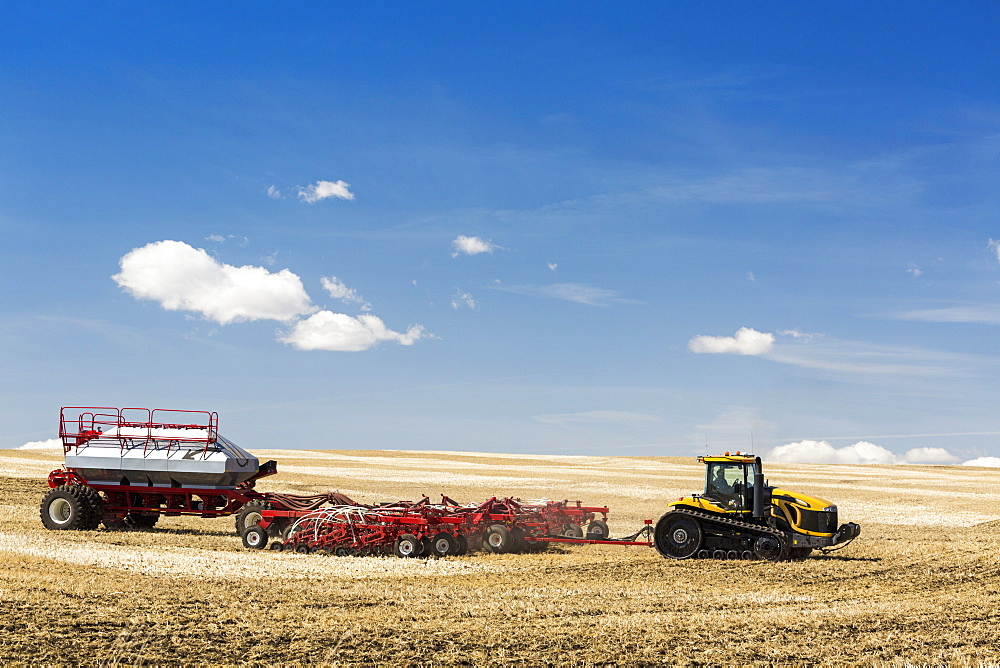 Tractor and air seeder in stubble field planting crop with blue sky and clouds, Alberta, Canada