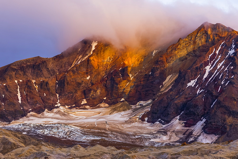 Trident Volcano rises above the ash-covered Knife Creek Glaciers at sunset in Katmai National Park; Alaska, United States of America