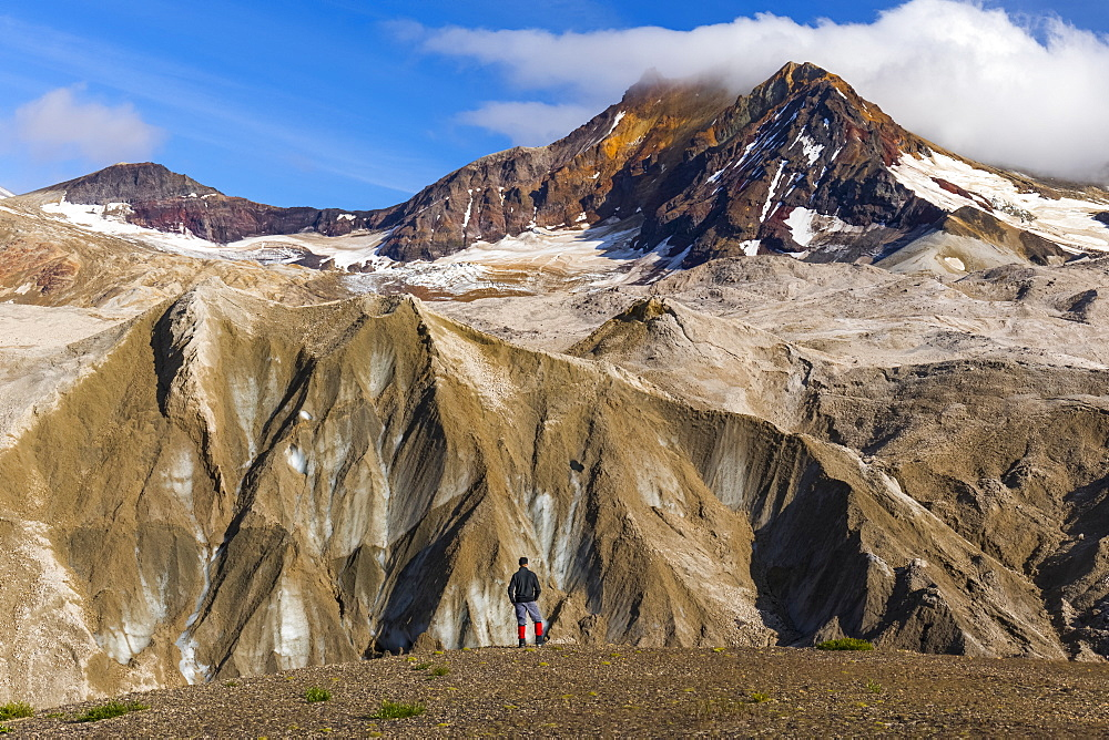 A man is dwarfed by the jagged, ash-covered Knife Creek Glaciers and Trident Volcano in the Valley of Ten Thousand Smokes in Katmai National Park; Alaska, United States of America - 1116-39557