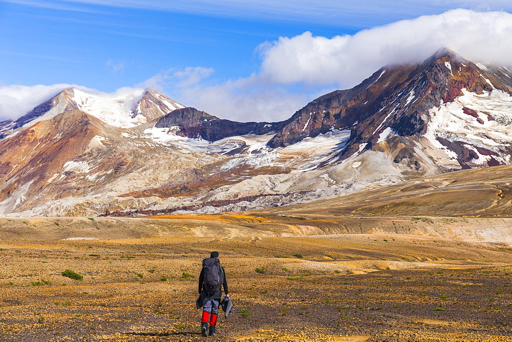 A backpacker crosses the exotic landscape of the ash and pumice-covered Valley of Ten Thousand Smokes in Katmai National Park, with Mt. Katmai (left), Trident Volcano (right), and the Knife Creek Glaciers looming in the distance; Alaska, United States of - 1116-39560