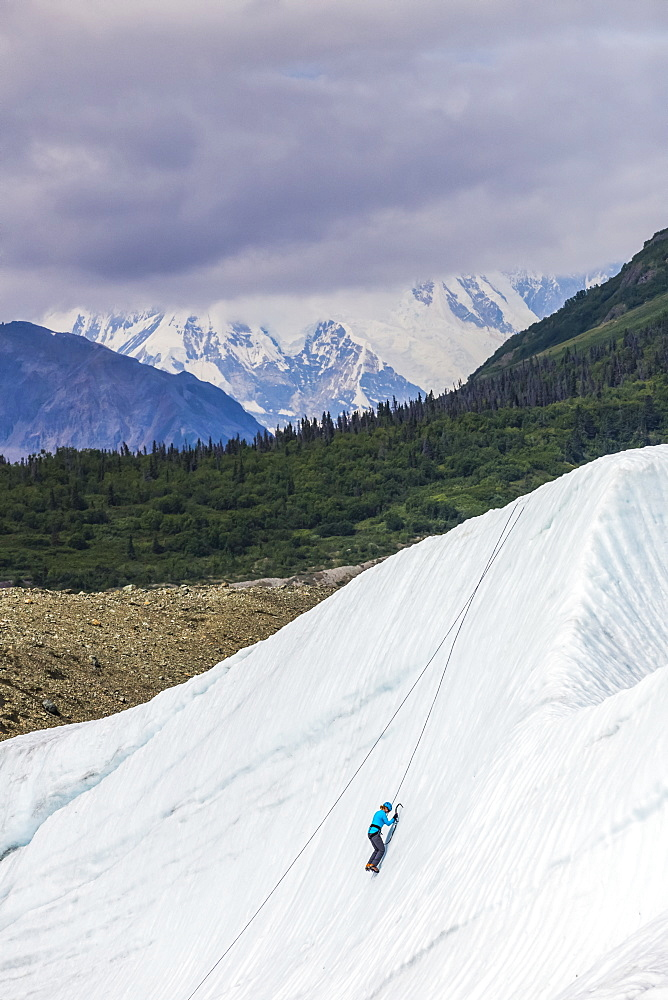 A woman ice climbs on Root Glacier in Wrangell-St. Elias National Park with Mt. Blackburn in the background; Alaska, United States of America