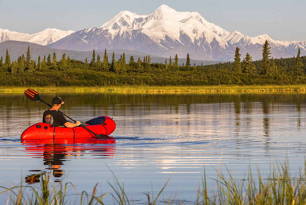 A man paddles a pack raft across Donnelly Lake with Mt. Hayes towering in the distance; Alaska, United States of America - 1116-39567