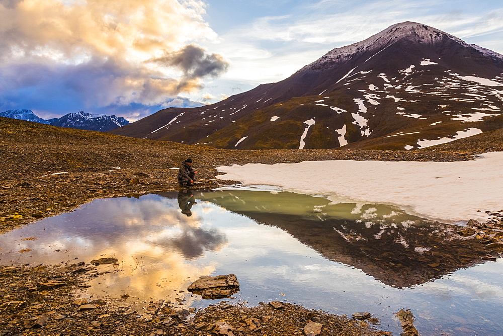 A backpacker pauses for rest beside a puddle while crossing over an unnamed pass in the Brooks Range under the midnight sun at 12:14 a.m.; Alaska, United States of America