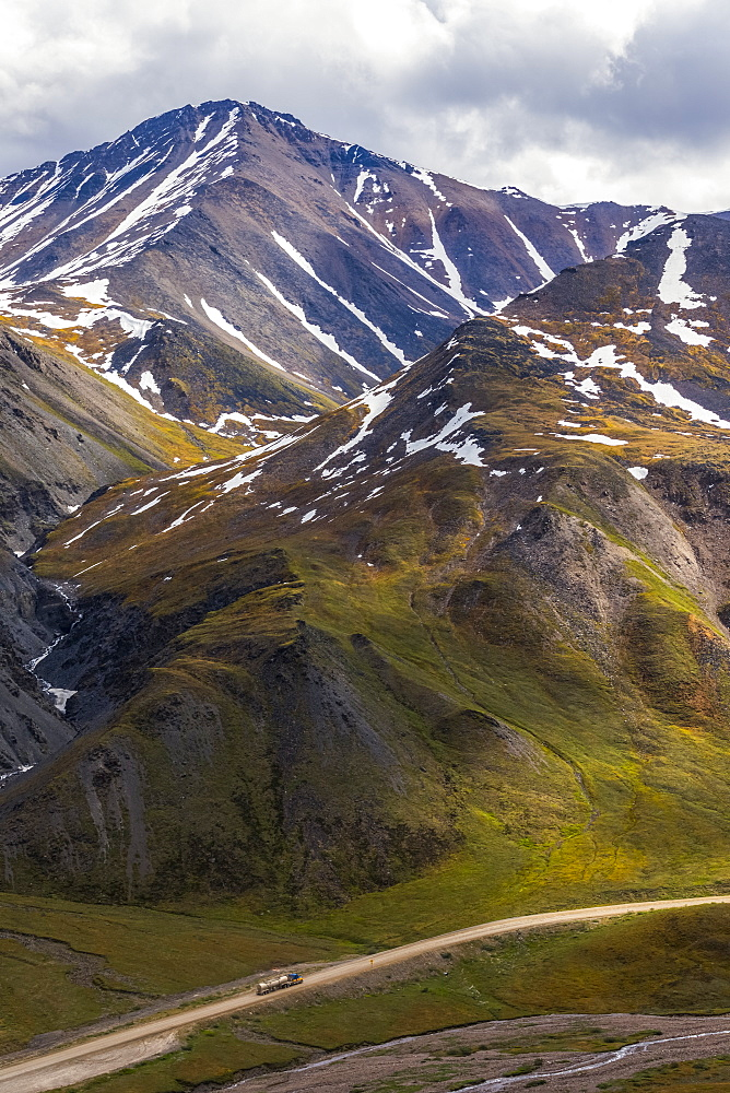 A truck approaches Atigun Pass along the Dalton Highway with the mountains of the Brooks Range towering overhead; Alaska, United States of America