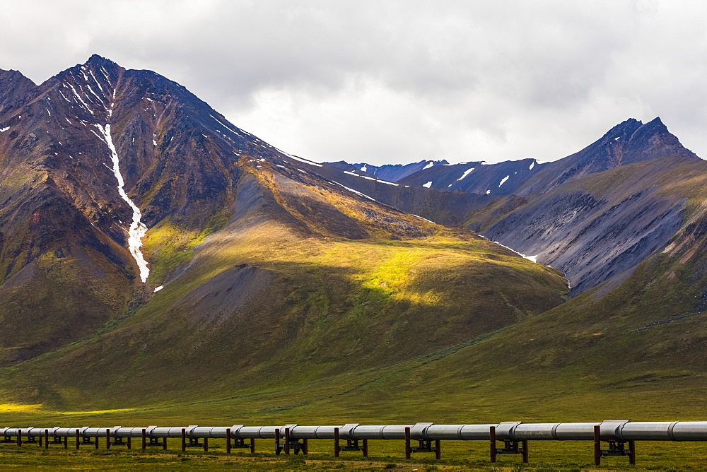 The Trans-Alaska Pipeline crosses over tundra beneath the mountains of the Brooks Range along the Dalton Highway; Alaska, United States of America
